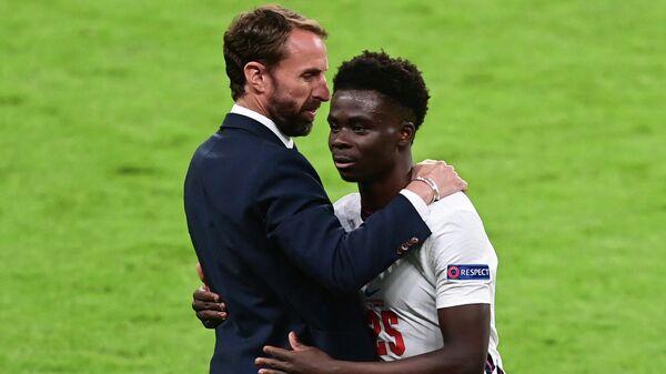 Полузащитник сборной Англии Букайо Сака (справа) и главный тренер команды Гарет Саутгейт
