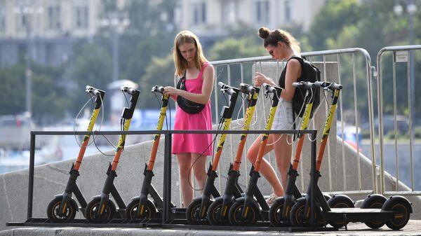 Девушки берут на прокат электросамокаты на набережной Москвы-реки в ЦПКиО имени Горького в Москве