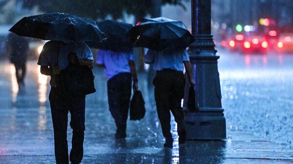 Прохожие на одной из улиц в Москве во время дождя