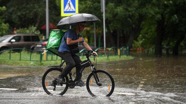 Мужчина едет на велосипеде по одной из улиц в Москве во время дождя