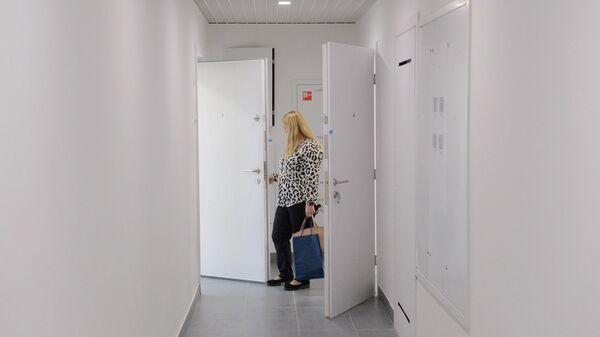 Девушка в коридоре многоэтажного жилого дома