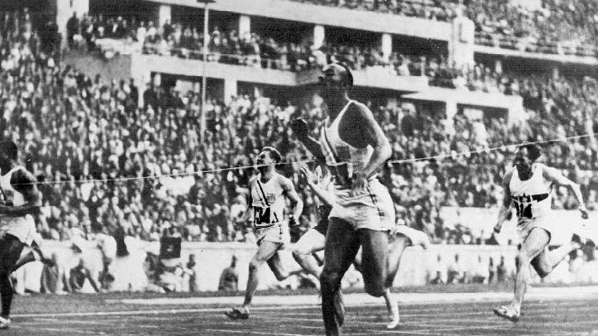 Американский атлет Джесси Оуэнс пересекает финишную черту в забеге на 100 метров на Олимпиаде 1936 года в Берлине - РИА Новости, 1920, 04.07.2021