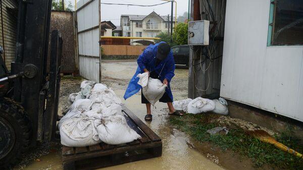 Мужчина укладывает мешки с песком во дворе своего дома на одной из улиц Хостинского района Сочи