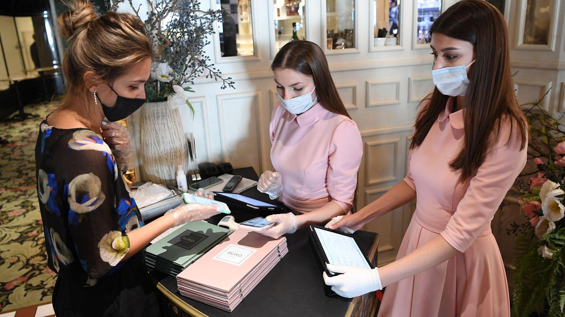 Хостес проверяет наличие и подлинность QR-кода у посетительницы перед посадкой за столик в ресторане BURO TSUM в Москве - РИА Новости, 1920, 07.07.2021