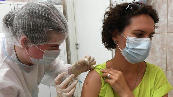 Медицинский работник и посетитель во время вакцинации против COVID-19 в Красноярске