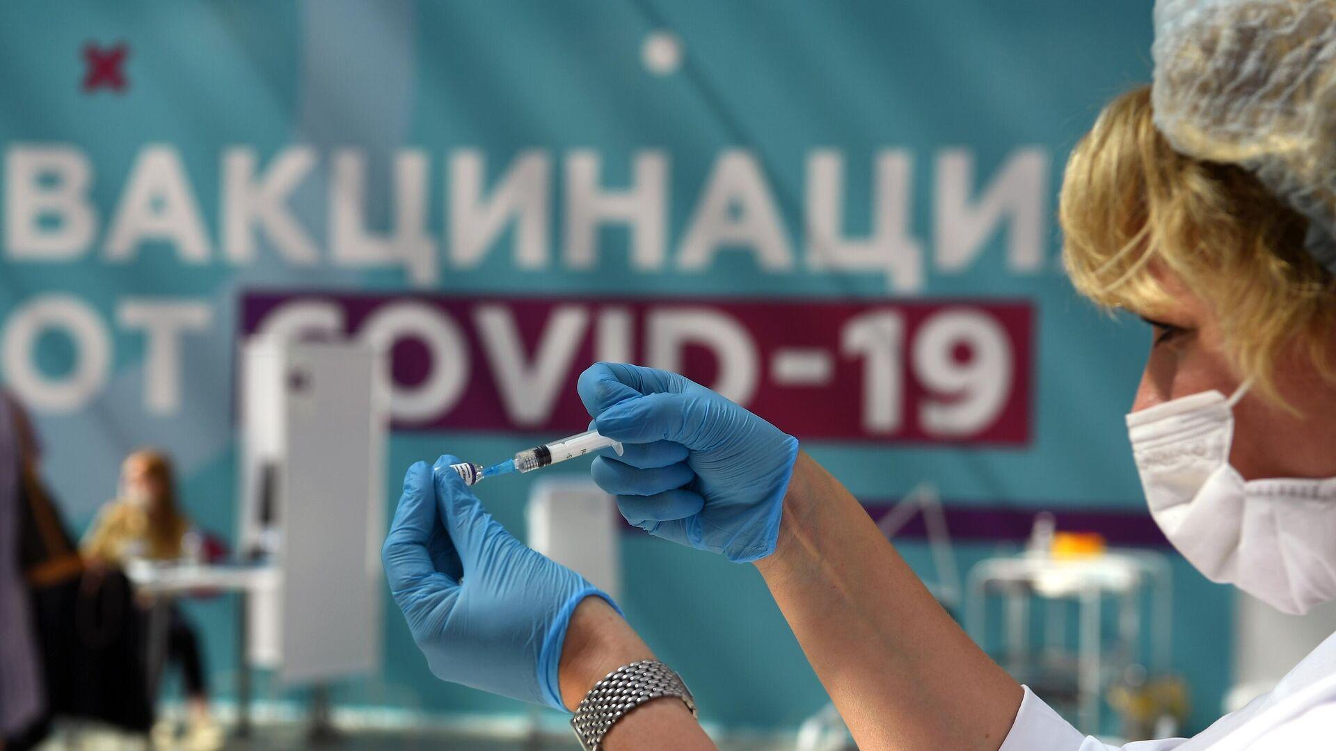 Медицинский сотрудник готовится сделать прививку посетителю в центре вакцинации от COVID-19 в Гостином дворе в Москве - РИА Новости, 1920, 14.07.2021