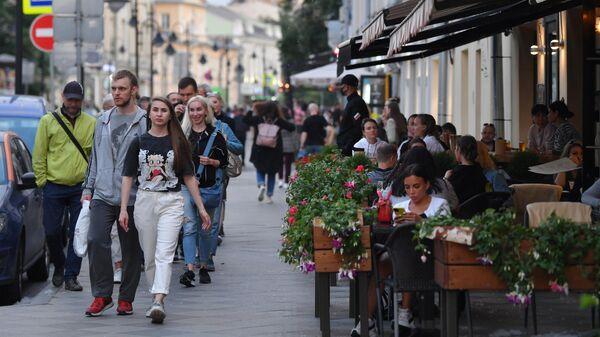 Прохожие идут мимо летней веранды кафе в Москве