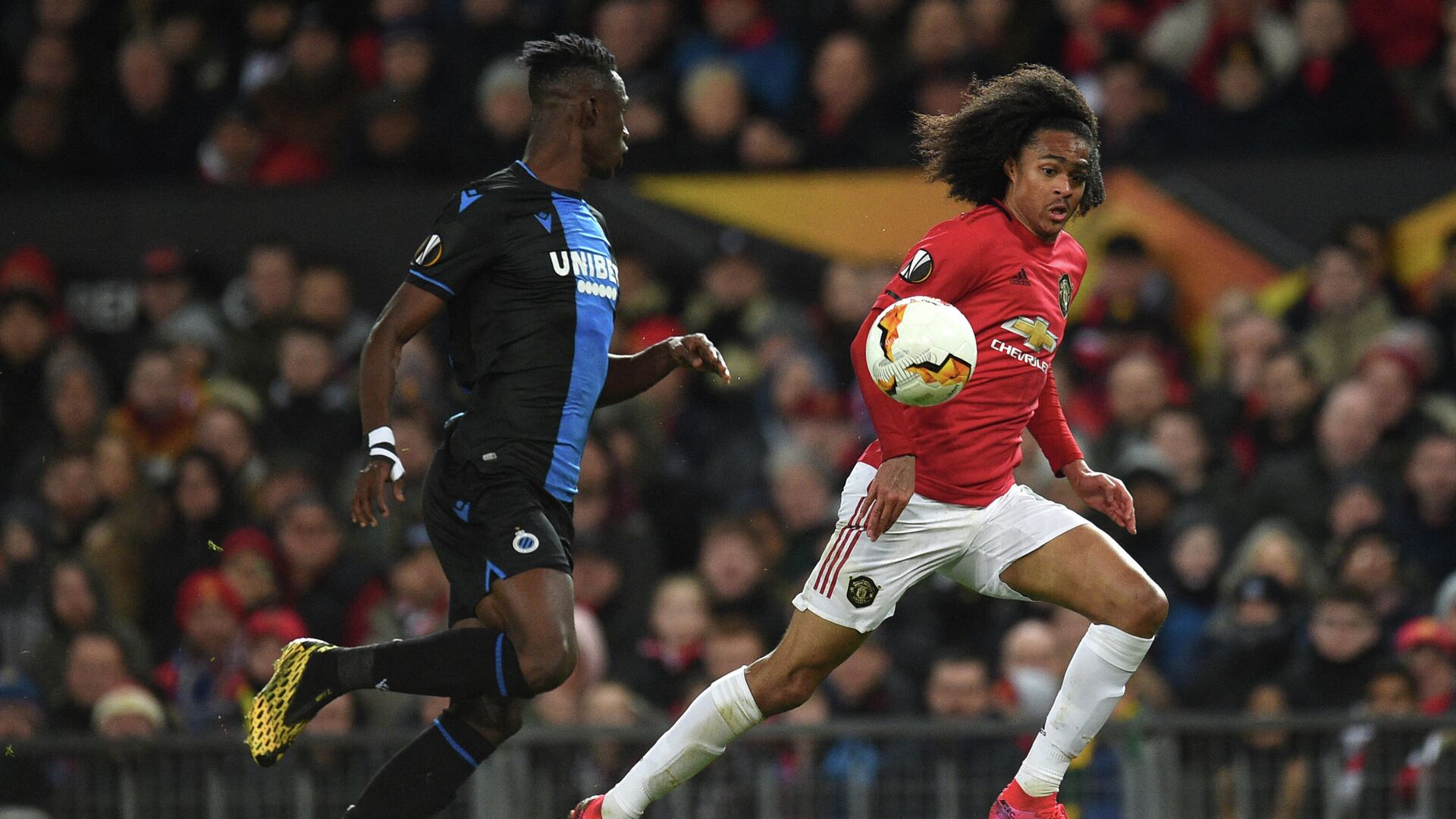 Club Brugge's Ivorian defender Odilon Kossounou (L) vies with Manchester United's Dutch midfielder Tahith Chong during the UEFA Europa League round of 32 second leg football match between Manchester United and Club Brugge at Old Trafford in Manchester, north west England, on February 27, 2020. (Photo by Oli SCARFF / AFP) - РИА Новости, 1920, 09.07.2021