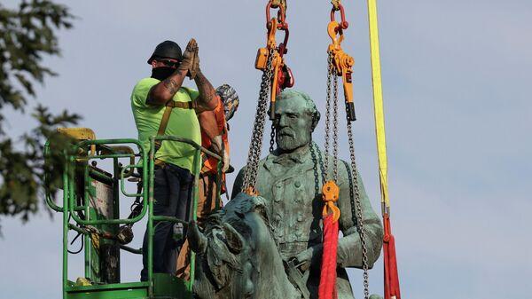 Рабочие снимают статую генерала Конфедерации Роберта Ли в Шарлоттсвилле, штат Вирджиния, США