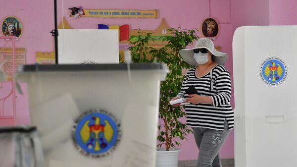Женщина голосует на избирательном участке в Кишиневе во время досрочных парламентских выборов в Молдавии