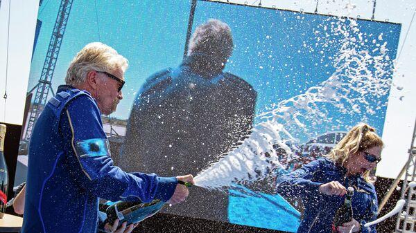 Ричард Брэнсон и главный астронавт-инструктор компании Virgin Galactic Бет Мозес после успешного возвращения космического корабля VSS Unity  на космодром Америка