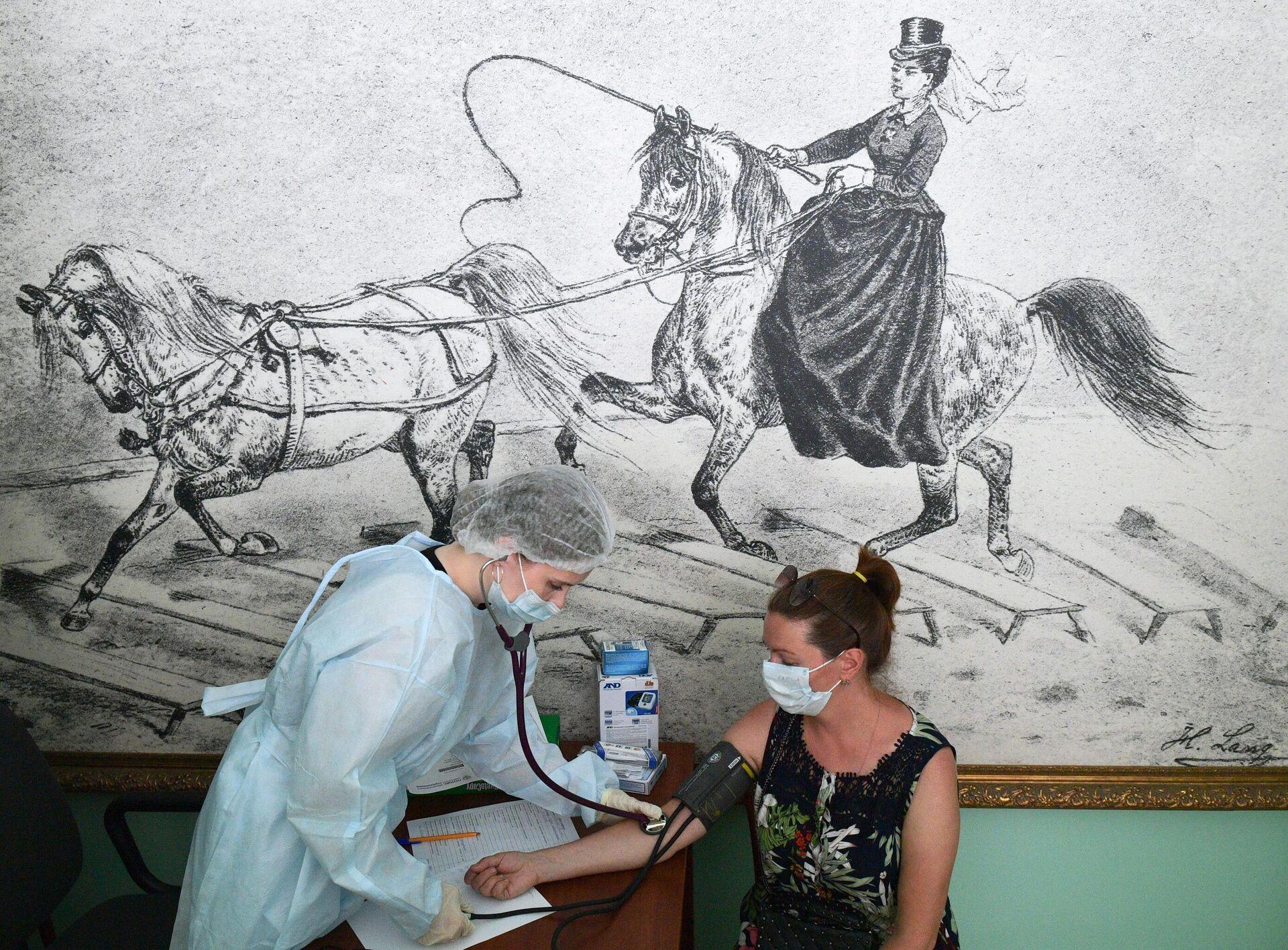 Медицинский сотрудник измеряет давление женщине перед вакцинацией от COVID-19 в Санкт-Петербурге - РИА Новости, 1920, 16.07.2021