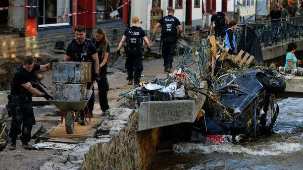 Полицейские и волонтеры убирают завалы в районе, пострадавшем от наводнения в Бад-Мюнстерайфеле, Германия
