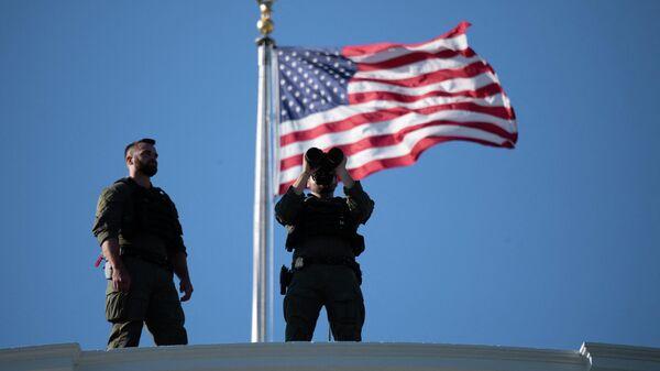 Военные с биноклем рядом с флагом США