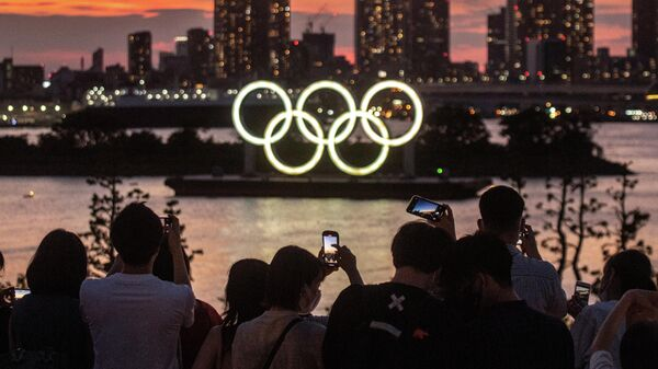 People take pictures as the Olympic rings lit up at dusk on the Odaiba waterfront in Tokyo on July 22, 2021 on the eve of the start of the Tokyo 2020 Olympic Games. (Photo by Philip FONG / AFP)