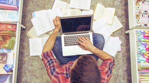 Студент с ноутбуком в библиотеке