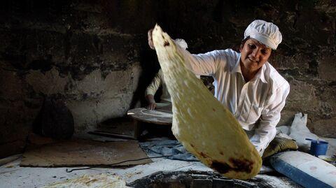 Женщина вынимает готовый лаваш из тандыра
