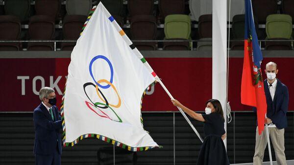 Президент Международного олимпийского комитета (МОК) Томас Бах передает олимпийский флаг мэру Парижа Анн Идальго