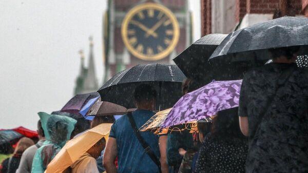 Люди под зонтами на Красной площади