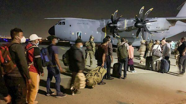 Люди ждут посадки на французской военный самолет в аэропорту Кабула, Афганистан
