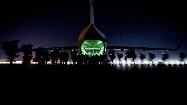 Американские военнослужащие готовятся к посадке на борт самолета C-17 Globemaster III ВВС США перед вылетом из международного аэропорта Хамида Карзая в Кабуле