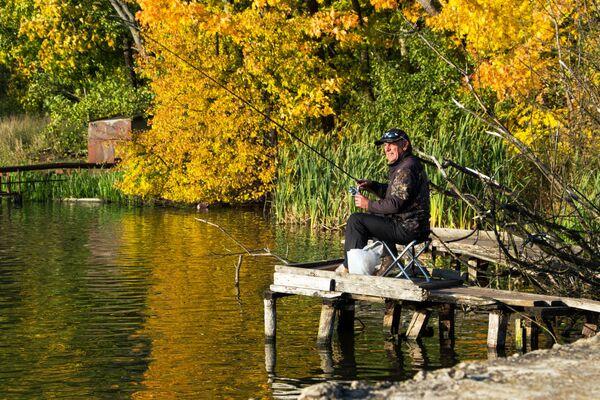 Мужчина ловит рыбу на территории усадебного парка Суханово в Московской области