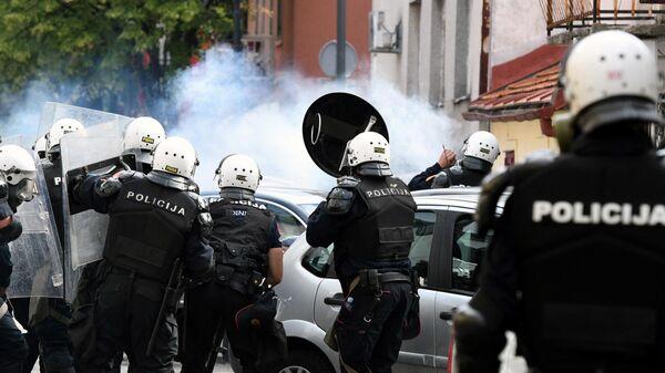 Сотрудники полиции стоят в облаке слезоточивого газа во время столкновений на акции протеста против интронизации митрополита Иоанникия