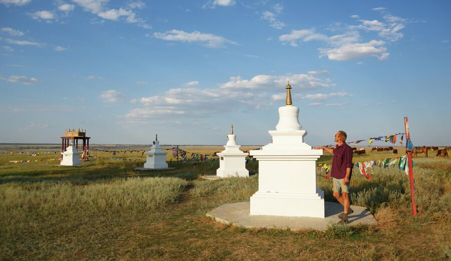 Мужчина совершает молитвенное обхождение восьми буддийских ступ, расположенных вокруг Одинокого Тополя