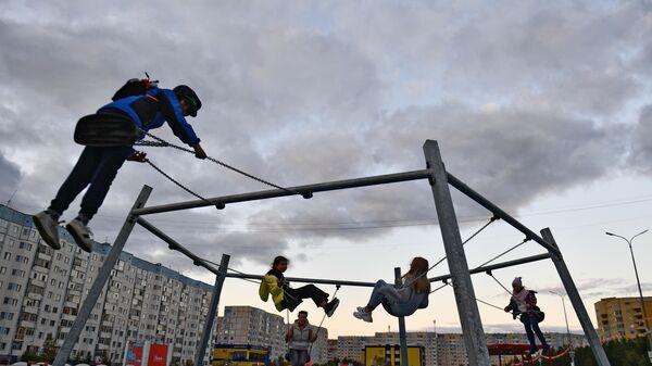 Дети качаются на качелях на площади у бульвара Стрижова в Надыме