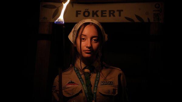 Девушка держит факел во время шествия, к которому присоединились десятки тысяч человек, Будапешт, Венгрия