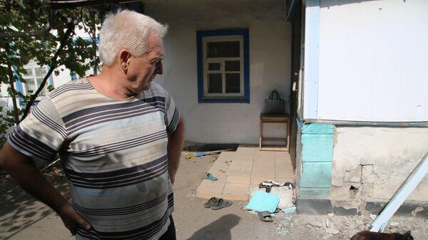 Мужчина во дворе дома, пострадавшего в результате обстрела, в поселке Еленовка Донецкой области
