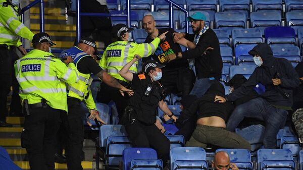 Police officers use batons as they hold back Napoli fans attempting to clash with Leicester fans after the final whistle during the UEFA Europa League Group C football match between Leicester City and Napoli at the King Power Stadium in Leicester, central England on September 16, 2021. - The match ended 2-2. (Photo by Oli SCARFF / AFP)