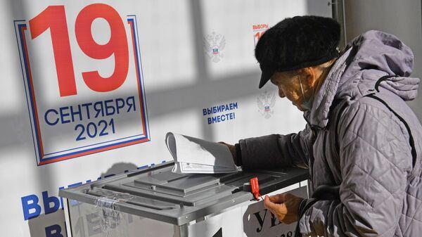 Пожилая женщина во время голосования на избирательном участке № 3381 в Москве