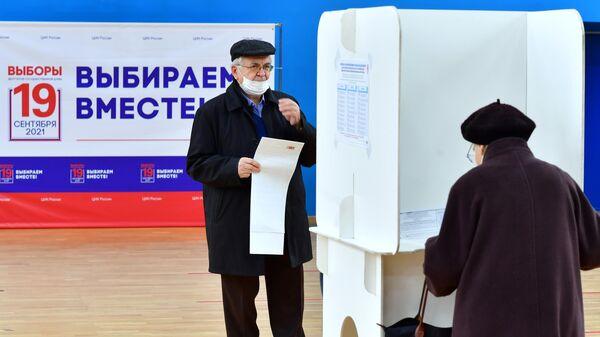 Люди голосуют на выборах депутатов Государственной Думы РФ в Москве