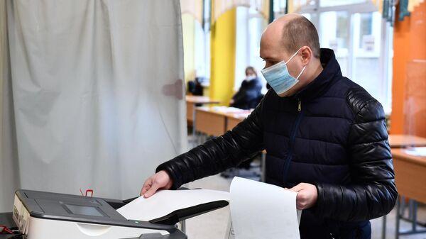 Мужчина голосует на выборах депутатов Государственной Думы РФ на избирательном участке в Екатеринбурге