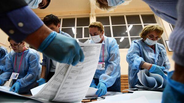 Члены избирательной комиссии подсчитывают бюллетени после закрытия избирательного участка