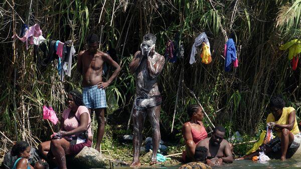 Гаитянские мигранты моются и стирают одежду на берегу Рио-Гранд после того, как они перебрались в Соединенные Штаты из Мексики