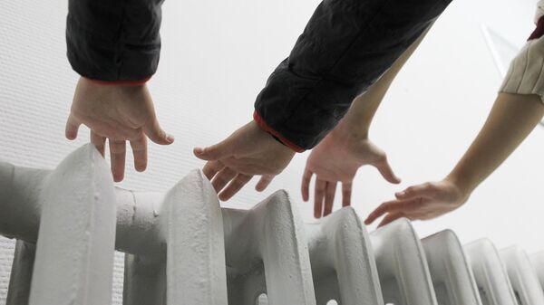 Люди держат руки над батареей, проверяя, включено ли отопление