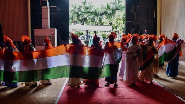 Женщины в традиционной одежде держат флаг по случаю празднования Дня независимости Индии в Бангалоре