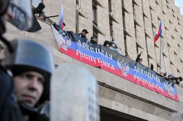 Участники митинга в Донецке, организованного сторонниками референдума о статусе региона, на здании областной администрации