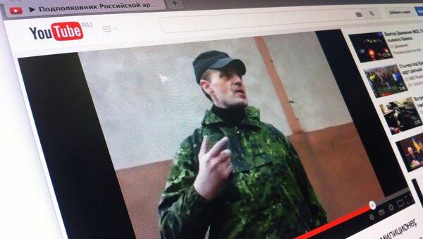 Кадр из видео, в котором мужчина в камуфляже представляется подполковником российской армии и отдает приказания сотрудникам милиции Горловки