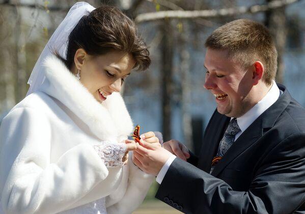 Молодожены завязывают ленточки на площади у мемориала Вечный огонь Славы в Иркутске