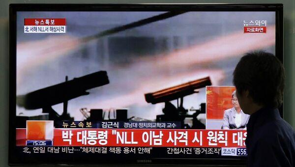 Мужчина на вокзале в Сеуле смотрит выпуск новостей о военных учениях КНДР
