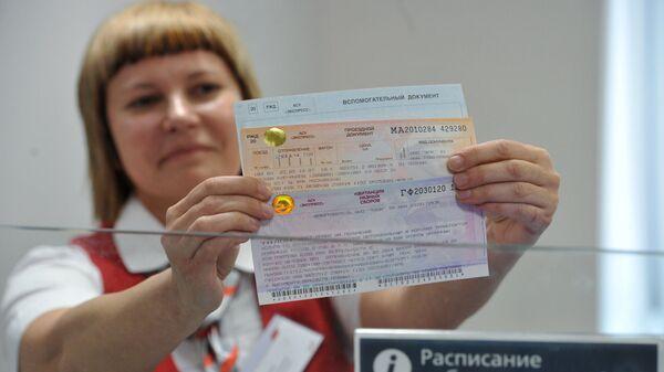 Билетный кассир держит в руках проездные документы в Крым