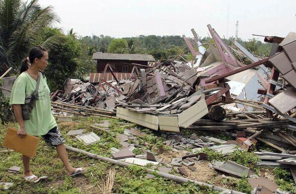 Женщина рядом со своим домом, разрушенным в результате землетрясения в Таиланде