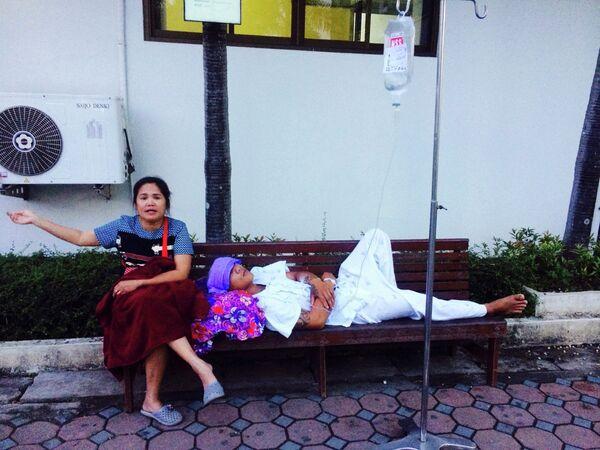Женщина рядом с эвакуированным из больницы пациентом во время землетрясения в Таиланде