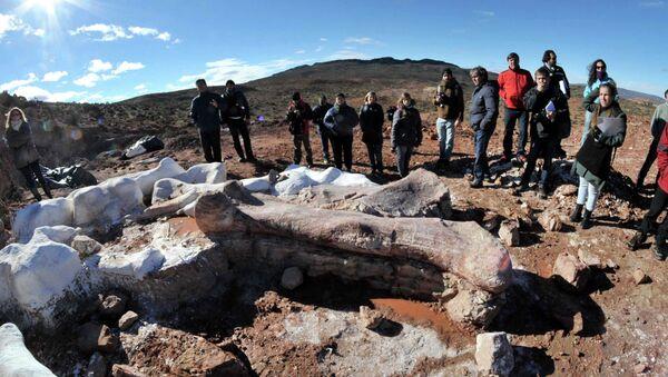 Люди стоят возле костей динозавтра недалеко от аргентинского города Трелью