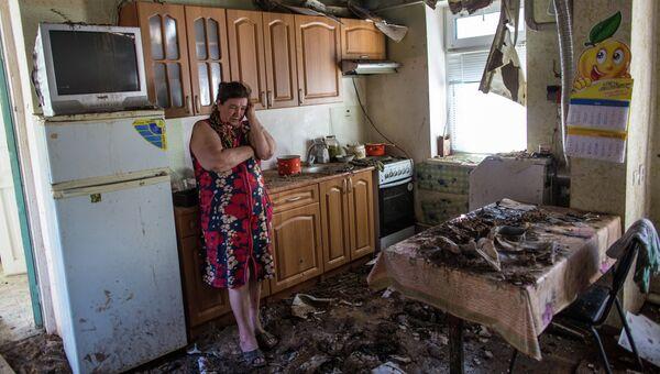 Женщина в своем доме, разрушенном в результате ночного артобстрела со стороны украинских военных на окраине Славянска. Архивное фото