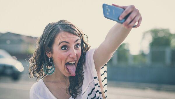 Девушка фотографируется на телефон. Архивное фото