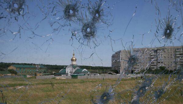 Вид на окраины Луганска через пробитое пулями стекло